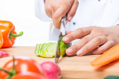 Cutting cucumber slices on a wooden board with a sharp knife Stock Image