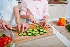 Cutting cucumber together Stock Photos