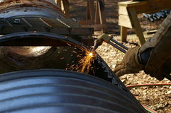 Cutting a culvert. Using a cutting torch to cut a hole in a galvanized culvert Stock Photo