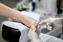 Cutting cuticle on foot, nail scissors Royalty Free Stock Photos