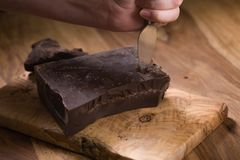 Cutting dark chocolate chunks on wood table. Shallow focus Stock Photos