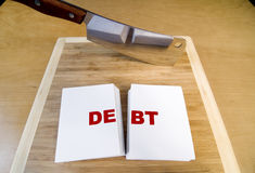 Cutting Debt. With a cleaver and cutting board Stock Image