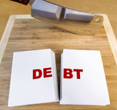 Cutting Debt. With a cleaver and cutting board royalty free stock image