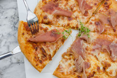 Cutting a delicious pizza. Ham cheese Stock Image