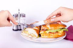 Cutting a delicius sandwich. Holding a knife and cutting a delicius sandwich Stock Images