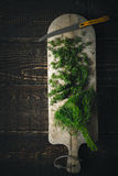 Cutting dill on the wooden board top view Royalty Free Stock Photo