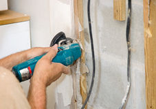 Cutting Drywall. Contractor using an angle grinder to cut drywall.  (White specs in image are construction dust, not noise).  Authentic and accurate content Royalty Free Stock Photo