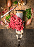 Minced meat in vintage grinder on background of herbs and spices Royalty Free Stock Image
