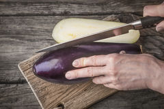 Cutting eggplants  on the wooden board. On the table top view Royalty Free Stock Image