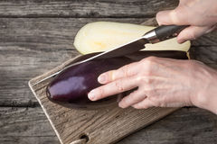 Cutting eggplants  on the wooden board top view. Cutting eggplants  on the wooden board on the table top view horizontal Royalty Free Stock Photo