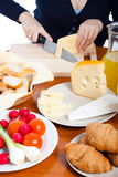 Cutting emmenthal cheese Stock Photography
