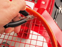 Cutting the excess of string of a Tennis racquet Stock Photo