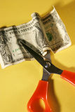 Cutting expenses. Scissors and money with yellow background Royalty Free Stock Image
