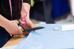 Cutting fabric with big old steel scissors Royalty Free Stock Images