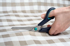 Cutting fabric closeup. Dressmaker at work. Fabric cutting scissors. Tailoring. Stock Image