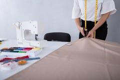 Cutting Fabric With för modeformgivare sax arkivbilder