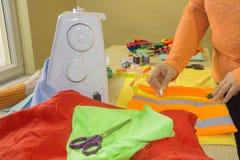 Cutting Fabric In för modeformgivare studio Skräddaren räcker arbete arkivbild