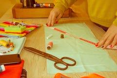 Cutting Fabric In för modeformgivare studio Skräddaren räcker arbete royaltyfri foto