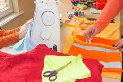 Cutting Fabric In för modeformgivare studio Skräddaren räcker arbete med mått Arbetsplats av sömmerskan royaltyfri bild