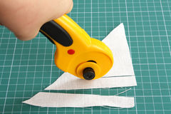 Cutting fabric with rotary cutter. On a measure mat Royalty Free Stock Images