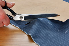 Cutting fabric for a suit. Photo of a piece of pinstripe material being cut around a bespoke template Stock Images