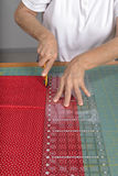 Cutting fabric for use in a quilt. A quilter uses a rotary cutter to cut fabric for a quilt Stock Photography
