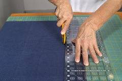 Cutting fabric for use in a quilt. A woman quilter cuts blue fabric with a rotary cutter for use in a new quilt Stock Photos