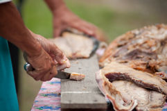 Cutting fish on wooden plank. View of hands cutting some dried fish on wooden plank Stock Images