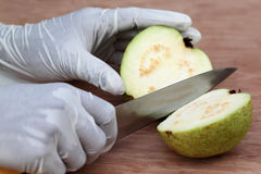 Cutting fresh guava on wooden surface Royalty Free Stock Images