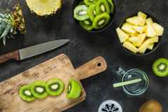 Cutting fresh kiwi and pineapple. Smoothie ingredients. Top view. Cutting fresh kiwi and pineapple on wooden board on dark background. Top view. Smoothie Royalty Free Stock Photography