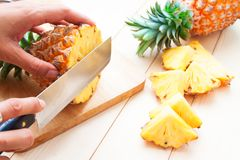 Cutting fresh pineapple on wooden table royalty free stock image