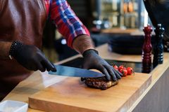 Cutting freshly cooked beef steak on a wooden board