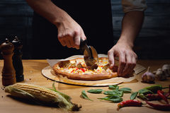 Cutting freshly cooked pizza. Chef cutting freshly baked hawaiian pizza. Low key shot, close up of hands, some ingredients around on table Stock Image