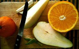 Cutting fruits. Orange, tangerine and pear during the preparation of a fruit salad stock photo