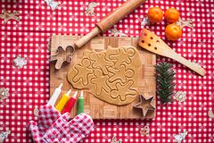 Cutting gingerbread cookie dough for Christmas and Royalty Free Stock Photos