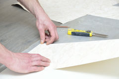 Cutting and glueing wallpaper Stock Photos