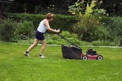 Cutting grass. Woman at work, cutting grass Royalty Free Stock Image