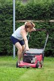 Cutting grass. Woman at work, cutting grass Stock Images