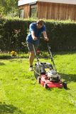 Cutting grass. Young man cutting grass at the front yard Royalty Free Stock Photos