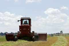 Cutting grass. Heavy agricultural machinery cutting a grass stock images
