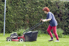 Cutting grass. There is a lot of work around the house in spring time Stock Photo