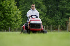 Cutting The Grass. A man cutting the grass on a garden tractor stock photography
