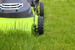 Cutting the grass with electric lawn mower Royalty Free Stock Images