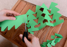 Cutting green card into a chain of Christmas trees Royalty Free Stock Photography