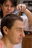 Cutting hair. Hairdresser cutting hair with clippers royalty free stock images
