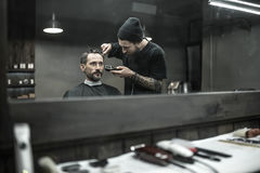 Cutting hair in barbershop. Peerless barber with a beard and a tattoo is cutting the hair of his bearded client in the barbershop. He is using a cutting comb and Royalty Free Stock Images