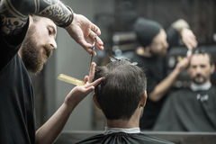 Cutting hair in barbershop Stock Photography