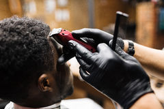 Cutting hair with clipper. Young man having his hair cut by clipper and comb royalty free stock photography