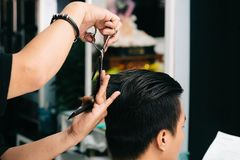Cutting hair. Close-up image of hair cutting process in barbershop Stock Photo