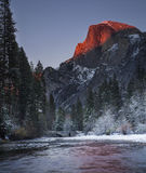 Cutting Half Dome. The sun gives Half Dome a beautiful display of alpenglow during an early winter's sunset in Yosemite National Park, California Stock Images